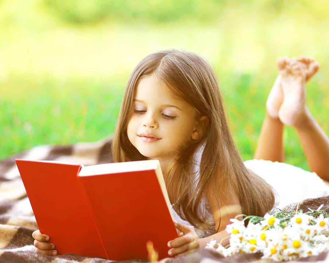 Girl-reading-book-on-the-grass